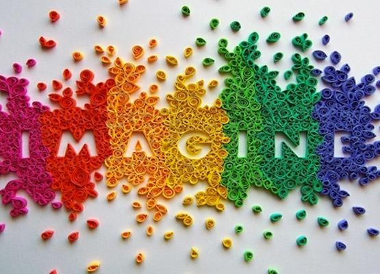 """Colorful display of magenta, red, orange, yellow, greens, and blues in flower petals spelling out the word """"IMAGINE"""""""